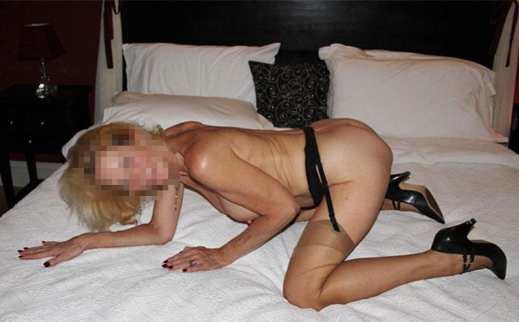 Donna matura nuda a pecorina sul letto con calze sexy