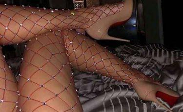 Gambe lunghe con calze a rete rosse e tacchi a spillo