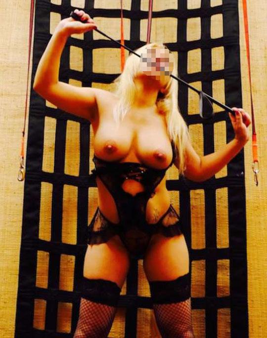 Mistress sexy e cattiva in completo nero con bacchetta per le punizioni