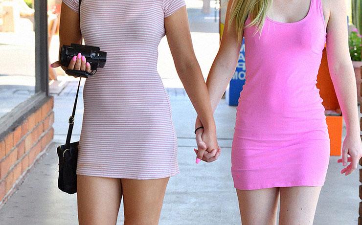 Coppia di amiche provocanti si tengono per mano indossano vestitino rosa
