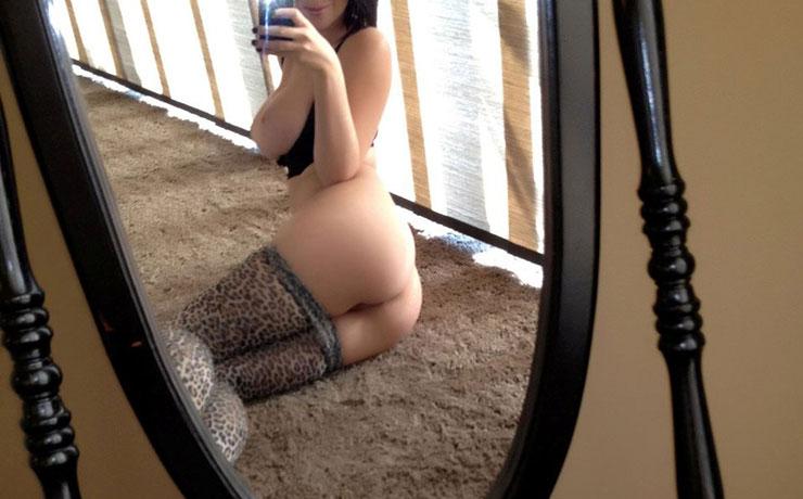 Ragazza maialina si fa un selfie allo specchio senza mutandine con collant abbassati e tette sode straripanti